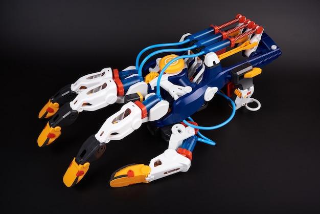Braço de robô de brinquedo de plástico com mecanismo de movimento hidráulico dos dedos. isolado no preto Foto Premium