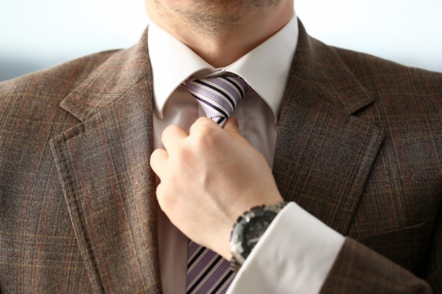 Braço masculino em terno marrom conjunto gravata closeup Foto Premium
