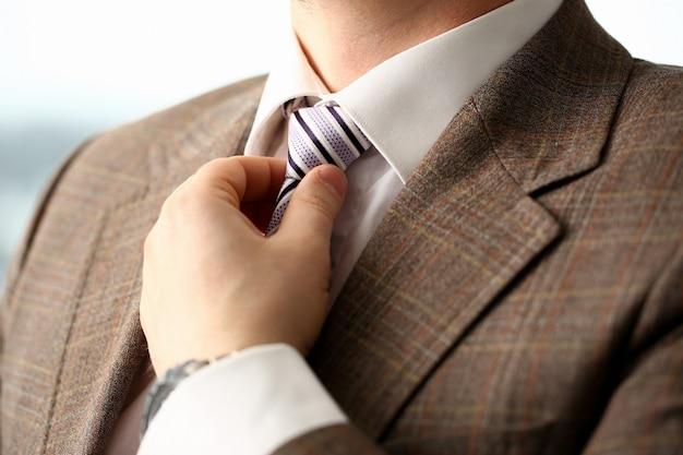 Braço masculino em terno marrom gravata closeup Foto Premium