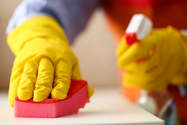 Braço na luva protetora de látex amarelo, limpando a poeira Foto Premium
