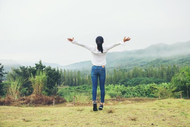 Braços abertos da mulher cheering no tempo do inverno do pico da montanha Foto Premium
