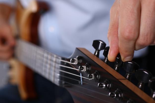 Braços masculinos tocando guitarra clássica de forma Foto Premium