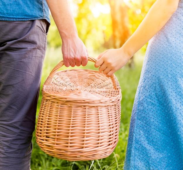 Braços, par, segurando, cesta piquenique, parque Foto gratuita
