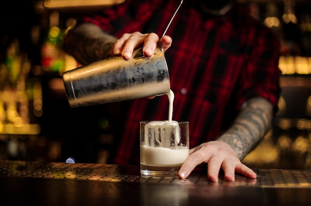 Braga, despejando uma bebida alcoólica cremosa grossa fresca em um copo Foto Premium