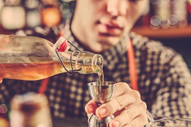 Braga, fazendo um cocktail alcoólico no balcão do bar Foto gratuita
