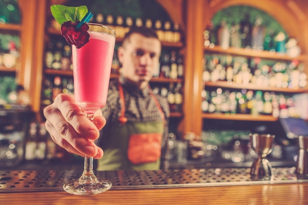 Braga, oferecendo um cocktail alcoólico no balcão do bar Foto gratuita