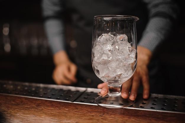 Braga, segurando um copo cheio de cubos de gelo Foto Premium