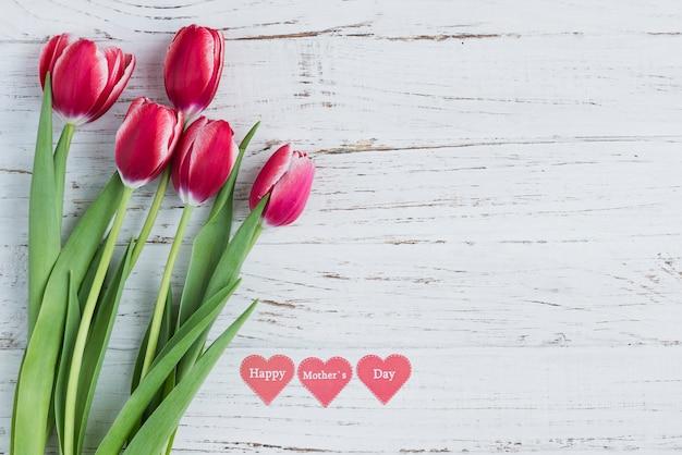 Branca superfície de madeira com tulipas e corações para o dia de mãe Foto gratuita