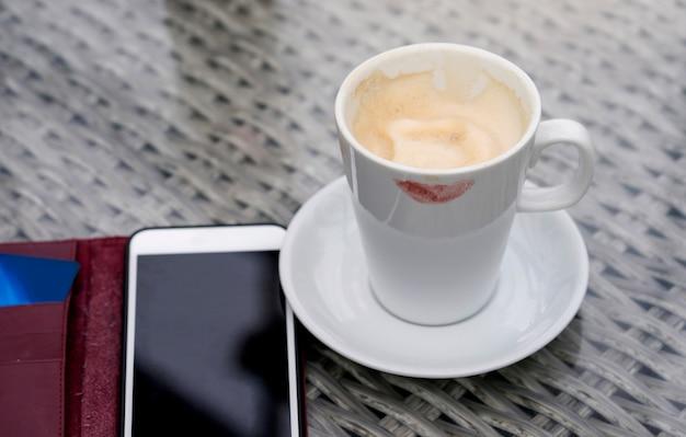 Branca, xícara café quente, com, marca, lábios, e, telefone móvel, ligado, a, tabela Foto Premium