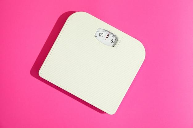 Branco pesar escalas em fundo rosa, espaço para texto Foto Premium