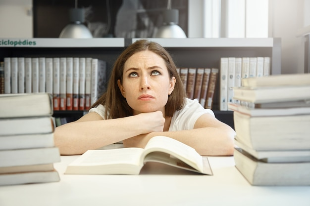 Brava aluna caucasiana com sobrancelhas tensas, olhando para cima, tentando se preparar para os exames e ler um manual, tendo olhar cansado e frustrado contra a biblioteca da universidade Foto gratuita