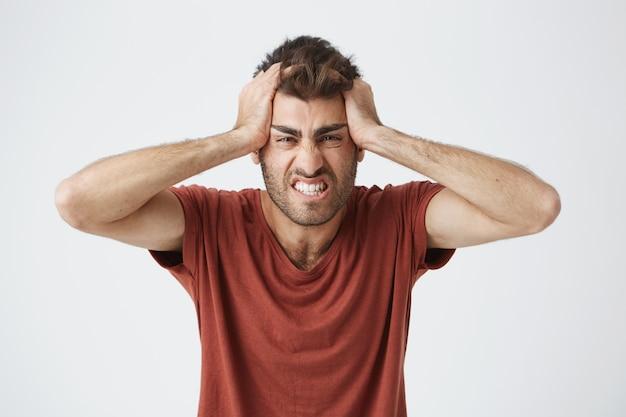 Bravo homem caucasiano bonito de camiseta vermelha, tendo expressões loucas, apertando a cabeça com as mãos mijadas de pessoas ao redor no trabalho. emoções negativas. Foto gratuita