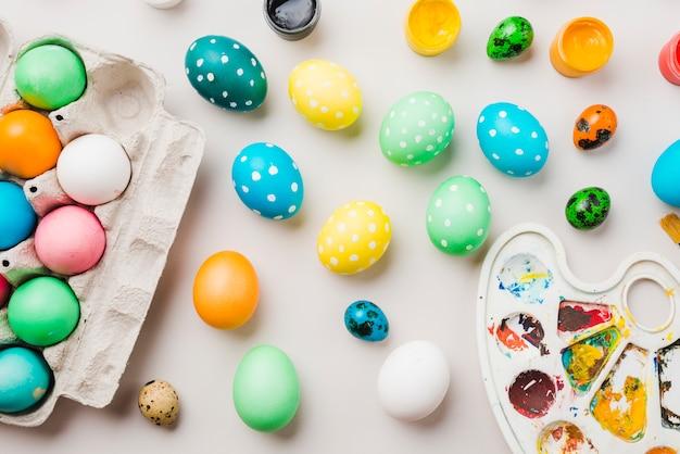 Brilhante coleção de ovos coloridos perto de recipiente, cores de água e paleta Foto gratuita