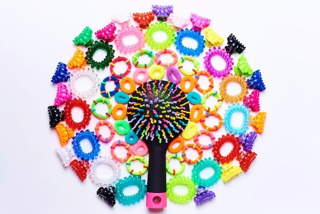 Brilhante multi pente colorido em um círculo de pequenos grampos de cabelo coloridos e elásticos para cabelo Foto Premium