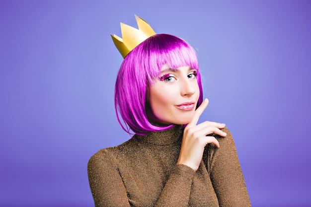Brilhante retrato elegante de uma jovem encantadora em coroa de ouro, cabelo roxo curto. comemorando ano novo, grande festa, emoções positivas, vestido de luxo, aniversário, carnaval. Foto gratuita