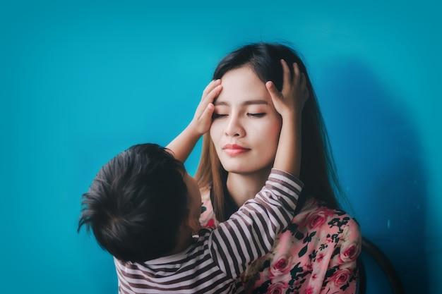 Brincadeira com a mãe sobre contra o fundo azul. Foto Premium