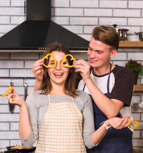 Brincalhão casal fazendo óculos de fatias de pimenta Foto gratuita