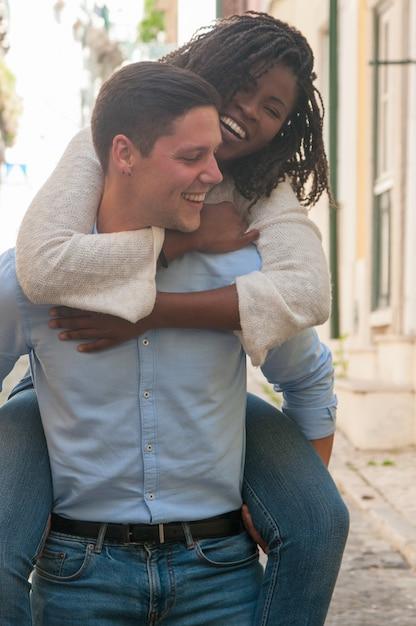 Brincalhão jovem carregando namorada nas costas ao ar livre Foto gratuita