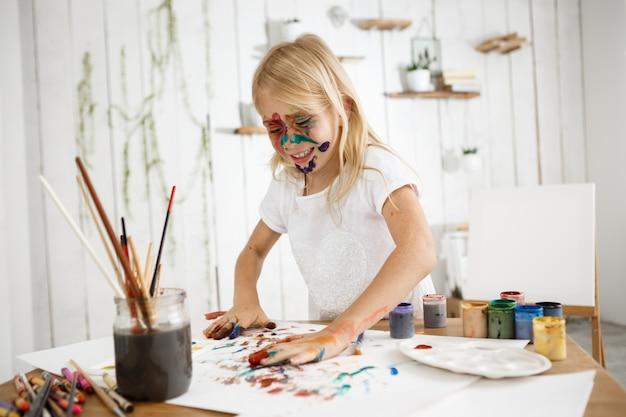 Brincalhão, linda garota loira se divertindo desenhando com as mãos, bipando as palmas das mãos em cores diferentes e colocando-as em uma folha de papel branca. Foto gratuita