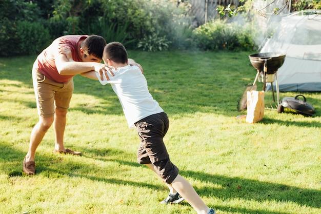 Brincalhão pai e filho brigando na grama no parque Foto gratuita