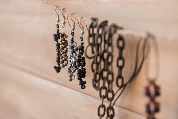 Brincos de miçangas e pulseira pendurado na corda contra a parede de madeira Foto gratuita