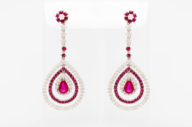 Brincos de ouro brancos com diamantes e pedras preciosas vermelhas sobre fundo claro. brincos compridos de ouro. acessórios de moda de luxo. Foto Premium