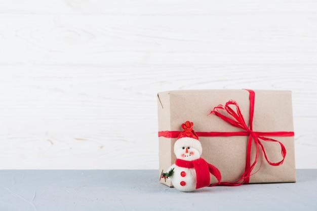 Brinquedo de boneco de neve com presente de natal embrulhado Foto gratuita