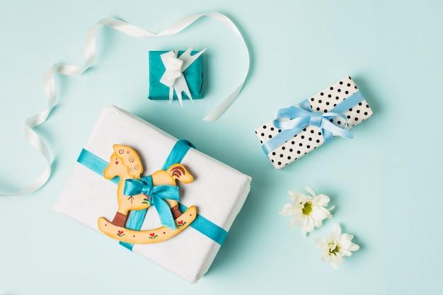 Brinquedo de cavalo de balanço com caixas de presente; flores e fita sobre o pano de fundo azul Foto gratuita