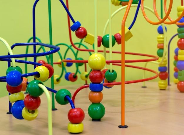 Brinquedo de lógica educacional de madeira com caminhos no bebê da criança na sala do berçário Foto Premium
