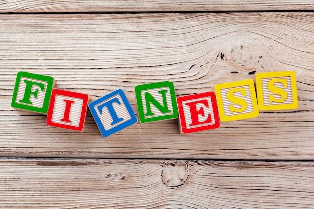 Brinquedo de madeira blocos com o texto: fitness Foto Premium