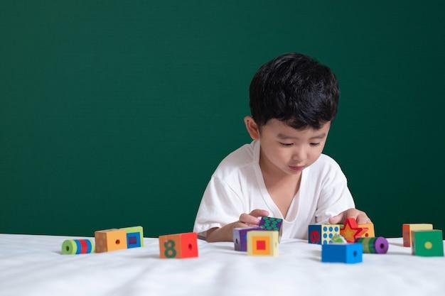 Brinquedo de menino asiático ou quebra-cabeça bloco quadrado em fundo verde lousa Foto Premium