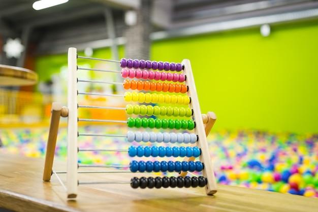 Brinquedo infantil de ábaco de madeira de cor brilhante na superfície da sala de jogos Foto Premium