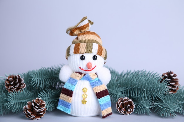Brinquedo pequeno boneco de neve em um galho de abeto de fundo cinza wuth Foto Premium