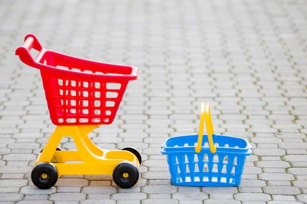 Brinquedos coloridos plásticos brilhantes, carrinho de compras e cesta ao ar livre num dia de verão ensolarado. Foto Premium