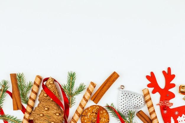Brinquedos de natal, doces, ramos de abeto e paus de canela Foto Premium