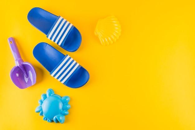 Brinquedos de praia e chinelos azuis sobre fundo amarelo Foto gratuita