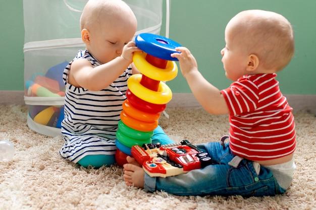 Brinquedos lógicos educacionais para crianças. criança recolhe pirâmide colorida. jogos para o desenvolvimento da criança. Foto Premium