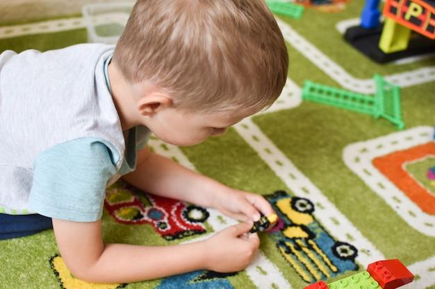 Brinquedos para meninos. criança com um trem no chão Foto Premium