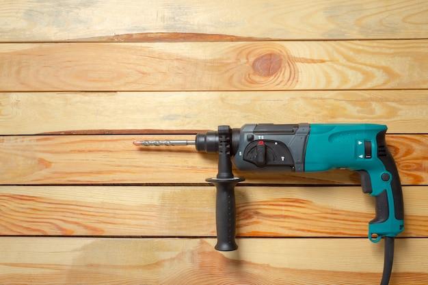 Broca de martelo elétrico encontra-se em uma mesa de madeira Foto Premium