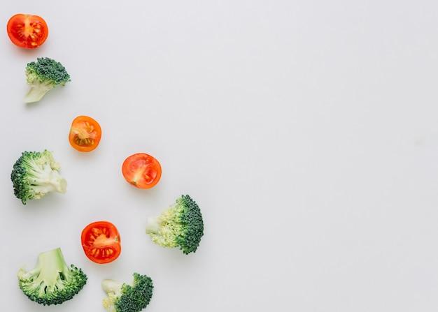 Brócolis frescos e tomates vermelhos cortados ao meio no fundo branco Foto gratuita