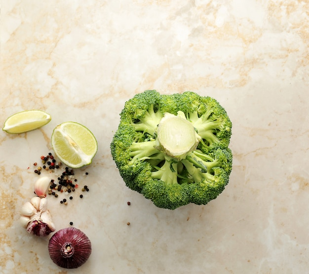 Brócolis, limão, alho e especiarias na mesa de mármore Foto Premium