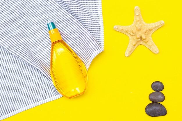 Bronzeamento em uma mesa amarela. bronzeado suave. corpo perfeito. a beleza . proteção solar. Foto Premium