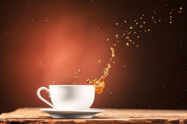 Brown espirra a bebida da xícara de chá em uma parede marrom Foto gratuita
