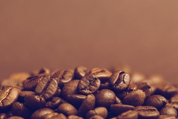 Brown roasted feijões de café no fundo escuro. espresso escuro, aroma, bebida de cafeína preta. copie o espaço Foto Premium
