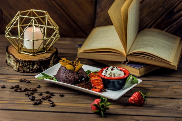 Brownies de chocolate servidos com molho cremoso e combinação de frutas Foto gratuita