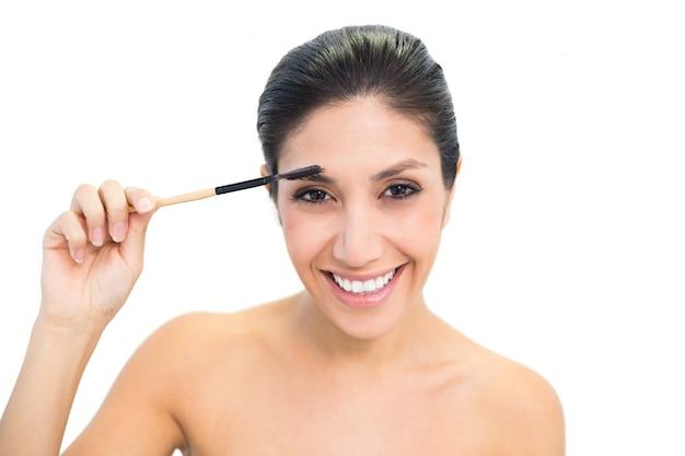 Brunette usando uma escova de sobrinho e sorrindo Foto Premium