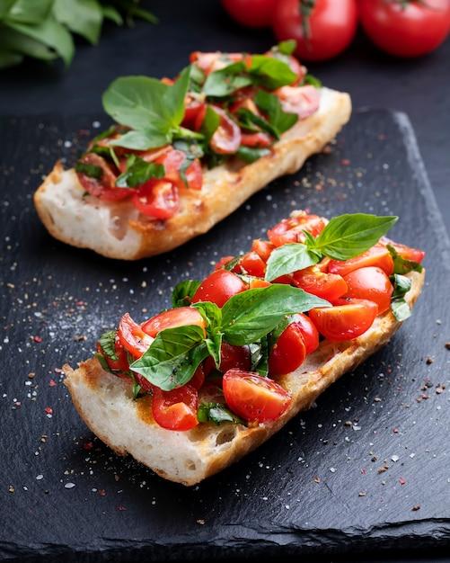Bruschetta caseira com tomate cereja e closeup de manjericão em uma placa de ardósia. cozinha italiana. antipasti. comida vegana Foto Premium