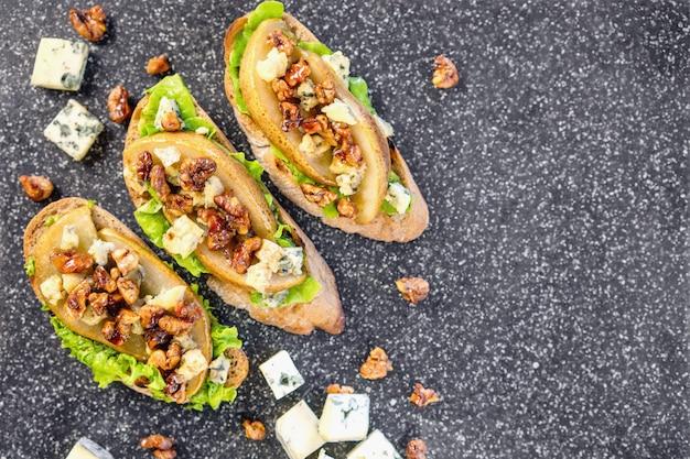 Bruschetta com pêra, mel, nozes, queijo, salada verde e azeite Foto Premium