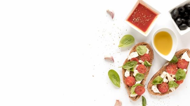 Bruschetta com queijo; tomate; folhas de manjericão no topo perto de molho; azeitonas; óleo e alho cravo sobre a superfície branca Foto gratuita