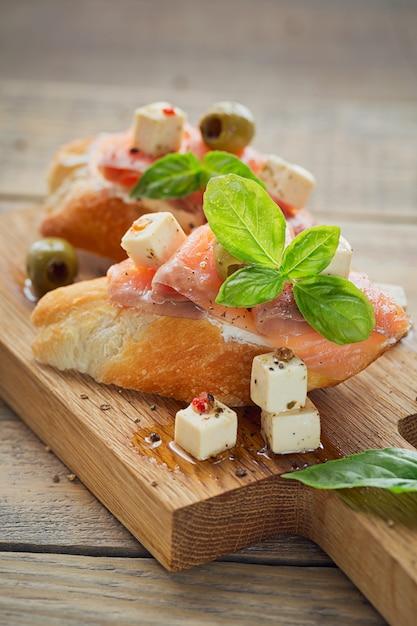 Bruschetta com salmão defumado, cream cheese, azeitonas e rúcula Foto Premium
